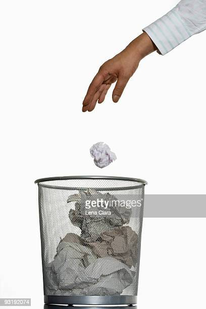 A human hand throwing a crumpled piece of paper into a wastepaper basket