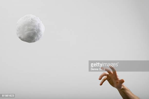 A human hand throwing a large cotton ball