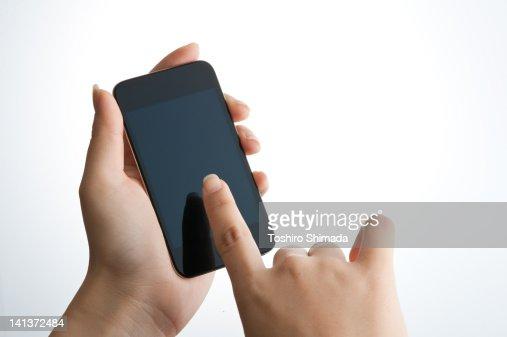 Human hand touching smart phone : Stock Photo