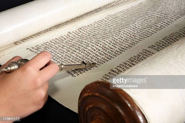 Human hand with a yad touching the torah.