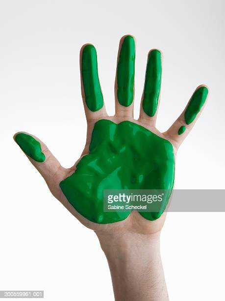 Human hand with green paint against white background, close-up