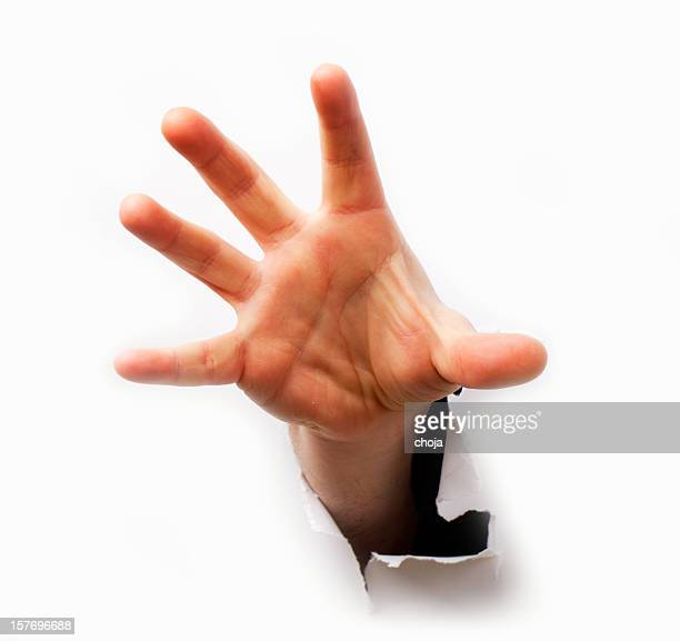 Human hand with opened fingers from hole in white background