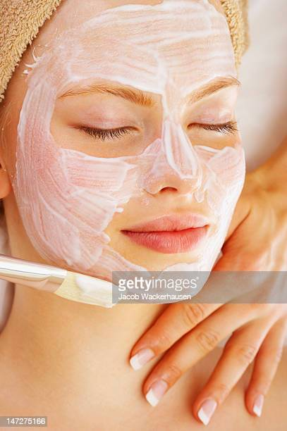 Menschliche Hände anwenden Gesichtsmaske auf eine junge Frau