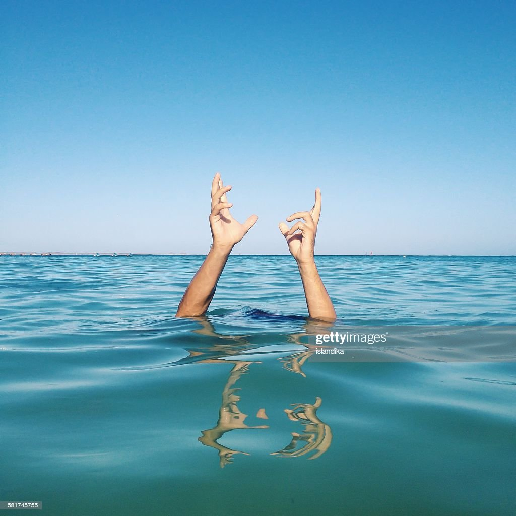 Human hands coming out of the sea