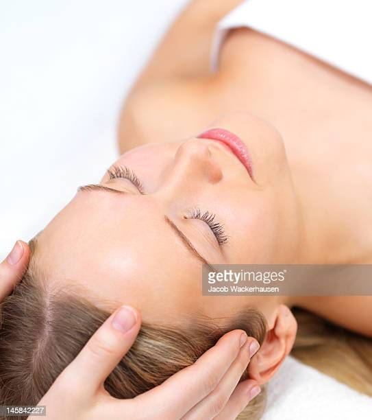 Human hands massaging female face at the spa