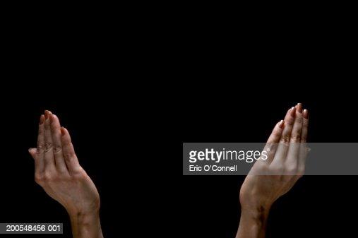 Human hands pleading, close-up, (digital composite)