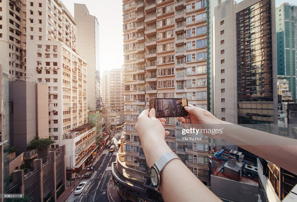 Human hands taking photo of city with smartphone