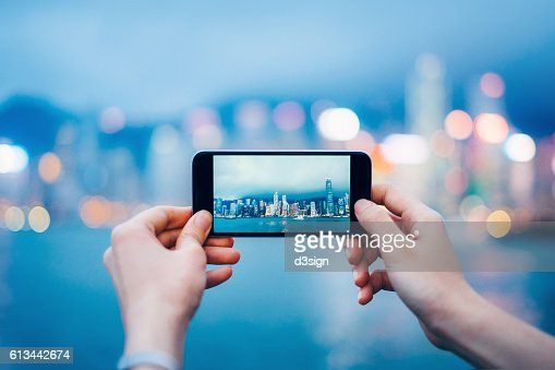 Human hands taking pictures with smartphone over Hong Kong cityscape and Victoria Harbour at sunset