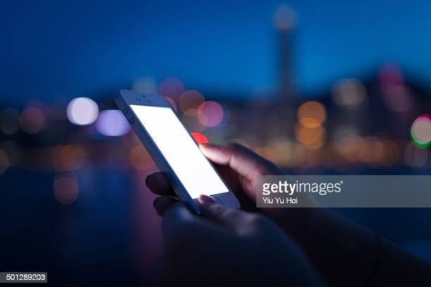 Human hands using smartphone in city at night time