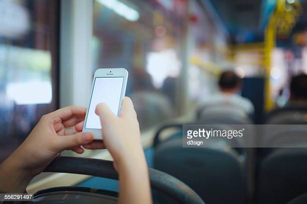 Human hands using smartphone on public bus in city