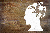 Human head as a set of puzzles on the wooden background