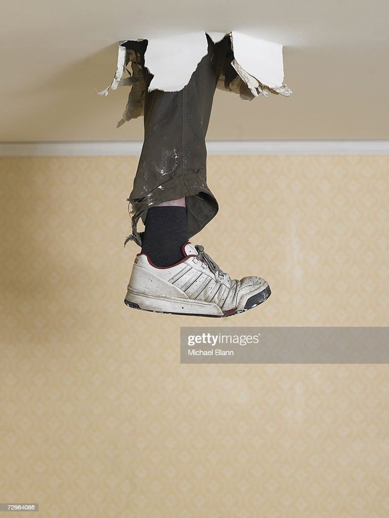 Human leg dangling from hole in ceiling : Stock Photo