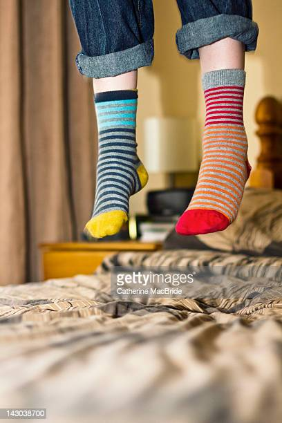 Human legs in sock jumping on bed