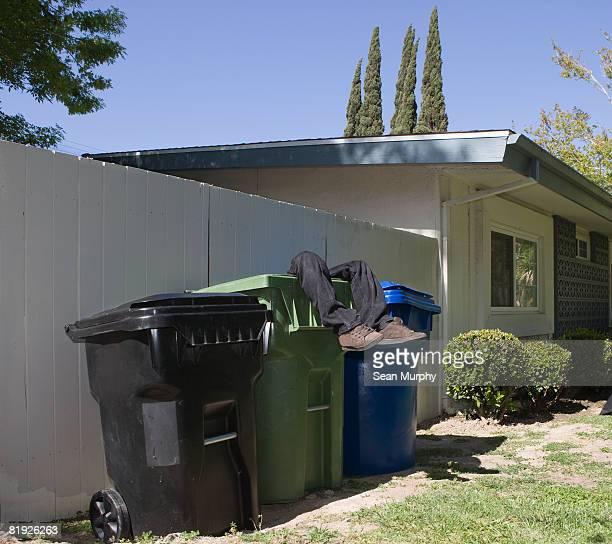 human legs protruding from a yard waste bin
