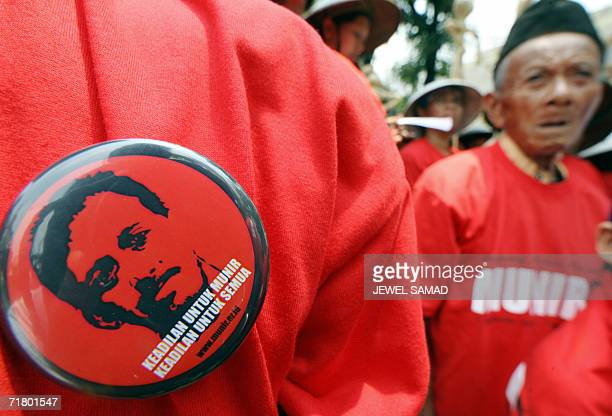 A human right activist wears a badge featuring an image of rights activists Munir as others shout slogans during a demonstration in Jakarta 07...