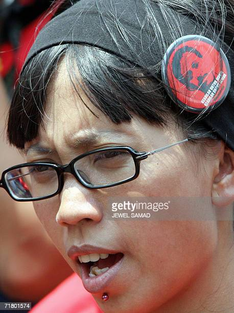 A human right activist wears a badge featuring an image of rights activist Munir with her headband as she shouts slogans during a demonstration in...