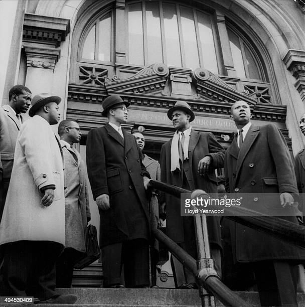 Human rights activist Malcolm X supporting some of his followers at the courthouse in Queens New York during a police brutality case circa 19551965