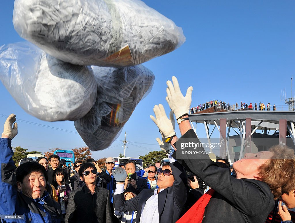 US human rights activist Suzanne Scholte (R) and former North Korean defectors release a balloon carrying anti-Pyongyang leaflets at Imjingak peace park in Paju near the Demilitarized Zone (DMZ) dividing the two Koreas on October 26, 2013. Activists launched balloons across the border carrying leaflets that criticise North Korea's ruling Kim family and demanding informations of US soldiers kept in North Korea during the Korean War.