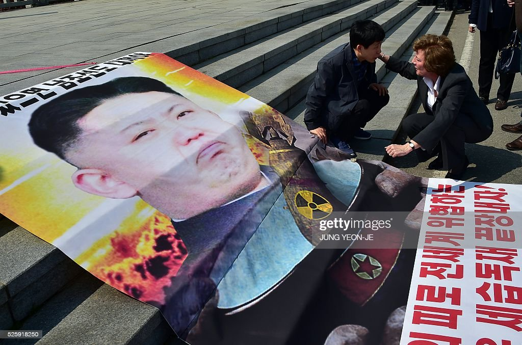 US human rights activist Suzanne Scholte (R) talks with Park Sang-Hak (2nd R), who heads a group of North Korean defectors, next to a banner showing North Korean leader Kim Jong-Un (L) before their press conference at Imjingak peace park in the border city of Paju on April 29, 2016. South Korean and US activists on April 29 launched anti-Pyongyang leaflets over the border where tensions have been running high since the isolated state's last nuclear test in January. / AFP / JUNG