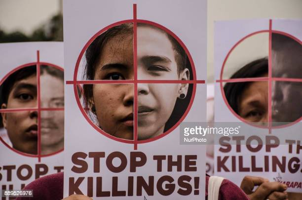 Human rights activists hold up posters with cutouts of crosshairs on one side and photos of extrajudicial killings on the other during the protest...