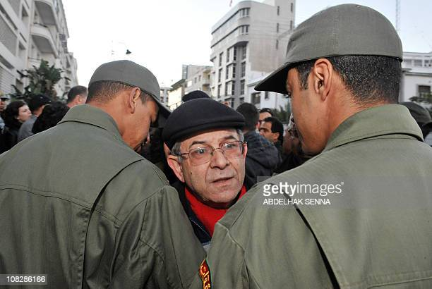 Human rights group leader Amine Abdelhamid is blocked by police forces during an unauthorized demonstration against the repression in Tunisia on...