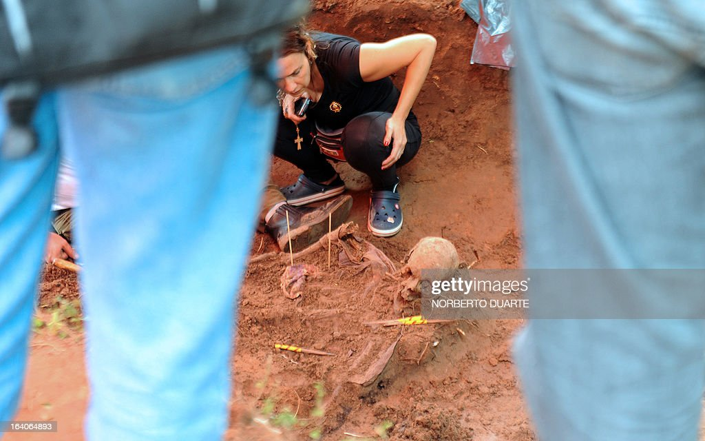 A human rights group member observes a human skull in the dirt on the premises of the Specialized Police Group headquarters in the outskirts of Asuncion on March 19, 2013. The human remains are believed to have been buried in the 1970´s, during the dictatorship of Alfredo Stroessner (1954-1989), in which hundreds went missing. AFP PHOTO/Norberto Duarte