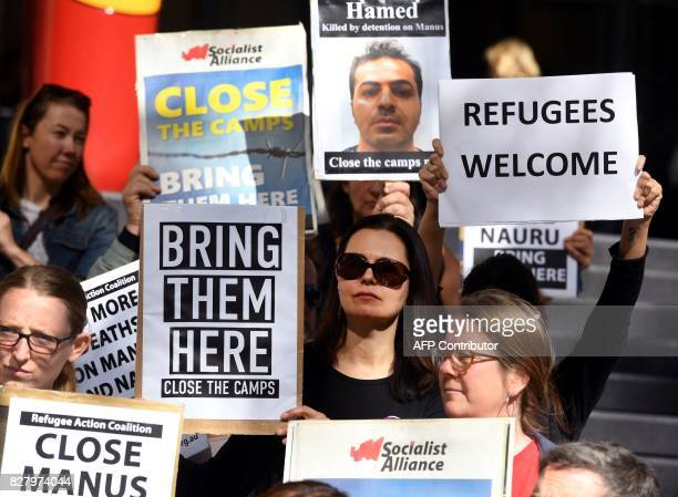 Human rights groups hold placards as they call for an independent inquiry outside the Commonwealth Government offices in Sydney on August 9 after...