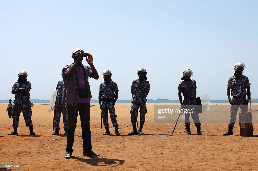 A human rights observer films, flanked by security forces, as journalists and opposition supporters attempted to hold a sit-in near the Presidency in Lome on March 14, 2013 to protest a law which has given the HAAC (High Authority of Audiovisual and Communication) more power. The protesters were forced away from the Presidency by security forces and several journalists were reportedly injured by tear gas and rubber bullets.