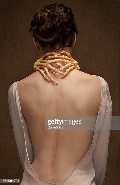 Human skeleton hand bones around neck of a woman
