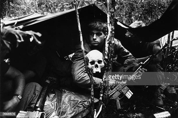 A human skull keeps watch over US soldiers encamped in the Vietnamese jungle during the Vietnam War