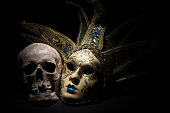 Human skull with venetian mask on a black background. Theater and drama concept.