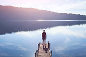 dreamer, silhouette of man standing on the lake wooden pier at sunset, human strength, psychology concept