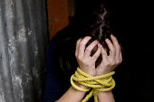Missing kidnapped, abused, hostage, victim woman with hands tied up with rope in emotional stress and pain, afraid, restricted, trapped, struggle, terrified, threaten, locked in a cage cell.