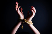 Close up of female hands tied in a rope