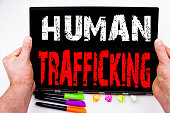 Human Trafficking text written on tablet, computer in the office with marker, pen, stationery. Business concept for Slavery Crime Prevention white background with space