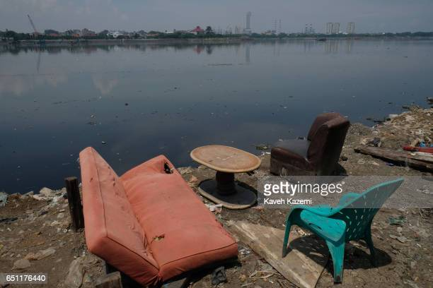Human waste seen floating in the river and on its bank in a old town slum where chairs and a worn out mattress and a table is arranged for evening...