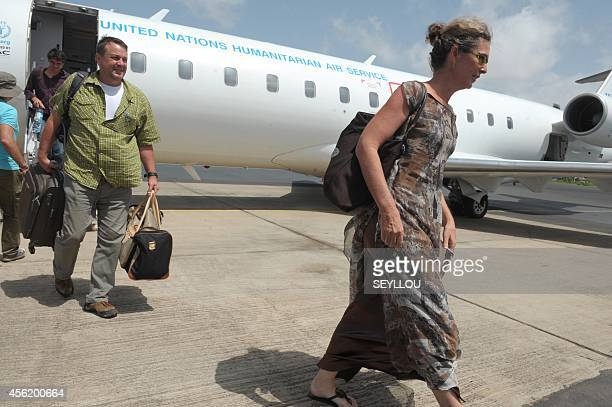 Humanitarian personnel leave a plane of the World Food Programme of the United Nations upon their arrival at the Dakar airport after flying from...
