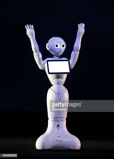 A humanlike robot called Pepper developed by SoftBank Corp's Aldebaran Robotics unit raises it's arms during a news conference in Urayasu Chiba...