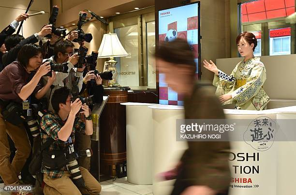 Humanoid ChihiraAico clad in a Japanese kimono greets a customer as photographers take pictures at an entrance of a department store in Tokyo on...