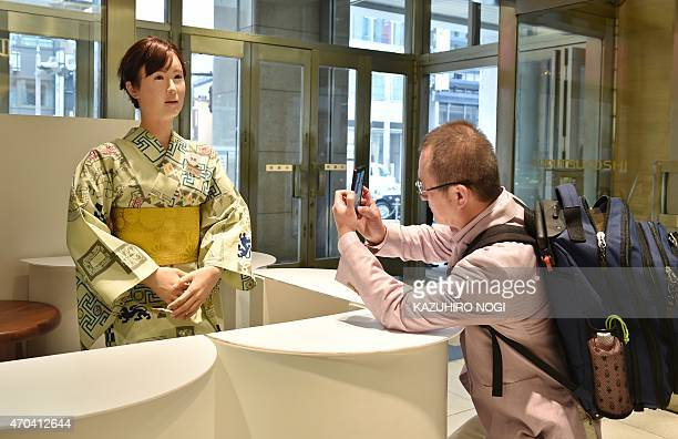 Humanoid ChihiraAico clad in a Japanese kimono greets a customer at an entrance of a department store in Tokyo on April 20 2015 She can smile she can...