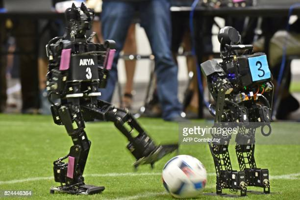 A humanoid from France's Bordeaux University codenamed Arya fights for the ball against a member of the Chinese team during their kidsize android...