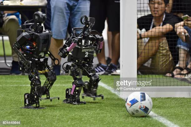 A humanoid from France's Bordeaux University moves toward the ball beside a humanoid from a Chinese team during their kidsize android football...