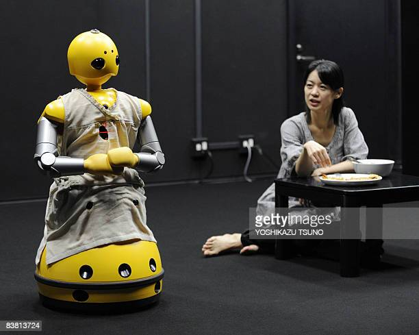 A humanoid robot Wakamaru produced by Japan's Mitsubishi Heavy Industry and named Momoko in the performance and actress Minako Inoue take part in a...