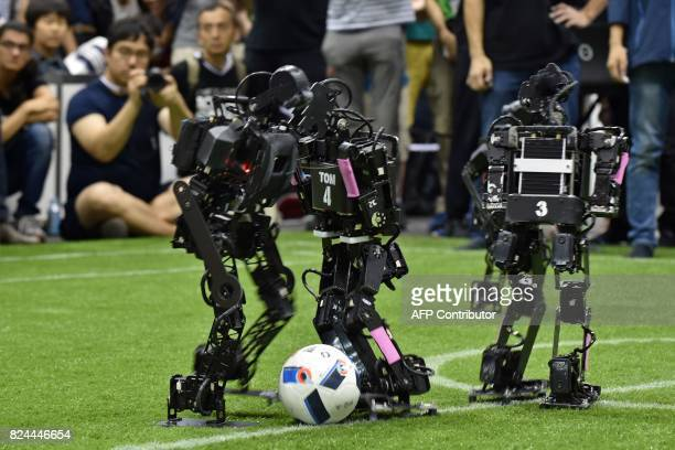 Humanoids from France's Bordeaux University fight for the ball with a member of the Chinese team during their kidsize android football tournament...