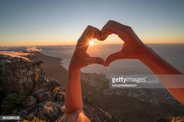 Human's hand making heart shape frame over coastline