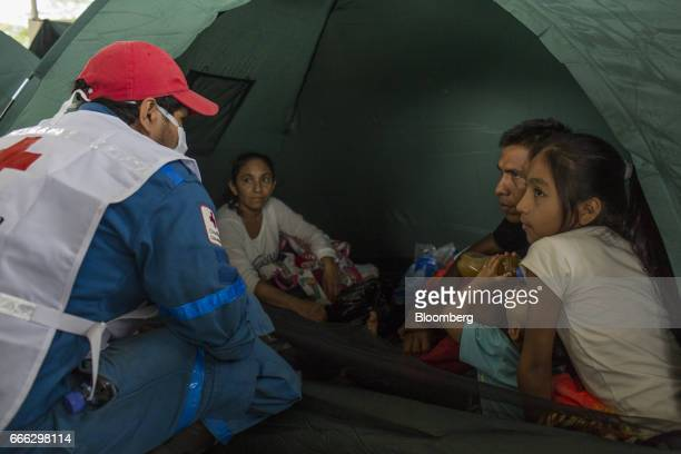 A humantarian aid worker speaks with a displaced family at a disaster relief center after a landslide in Mocoa Putumayo Colombia on Monday April 3...