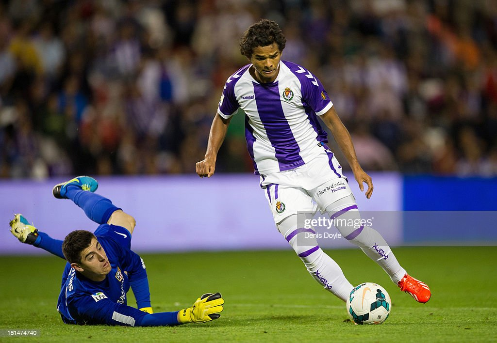 Humberto Osorio (R) of Real Valladolid CF beats <a gi-track='captionPersonalityLinkClicked' href=/galleries/search?phrase=Thibaut+Courtois&family=editorial&specificpeople=7126410 ng-click='$event.stopPropagation()'>Thibaut Courtois</a> of Club Atletico de Madrid during the La Liga match between Real Valladolid CF and Club Atletico de Madrid at Estadio Jose Zorilla on September 21, 2013 in Valladolid, Spain.
