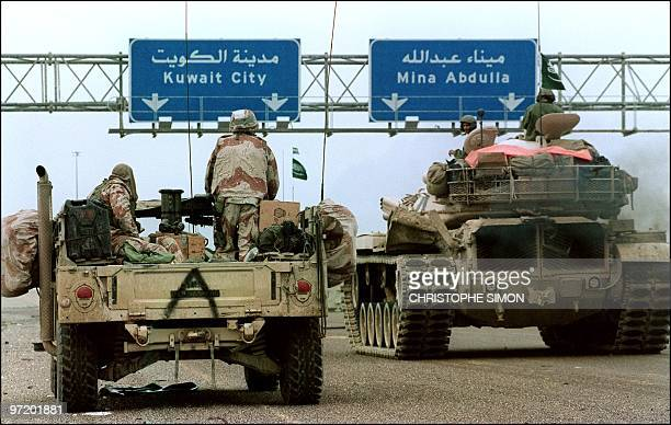 Hummvee jeep and a Saudi tank pass under a highway sign directing them to Kuwait City 26 February 1991 during Desert Storm Allied forces offensive