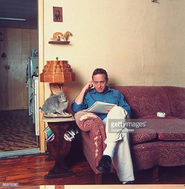 Humorist/writer David Sedaris eyeing a stuffed rabbit on end table as he sits on couch at home