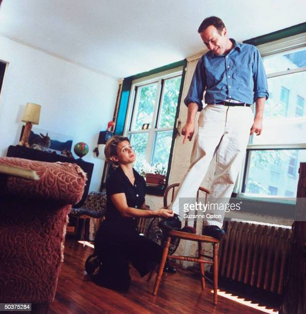Humorist/writer David Sedaris is standing on chair as his sister Amy adjusts the hem on his pants at his apt